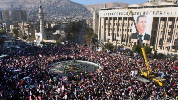 Pro-Syrian regime protesters gather during a protest against sanctions, in Damascus, Syria, on Friday December 2, 2011.