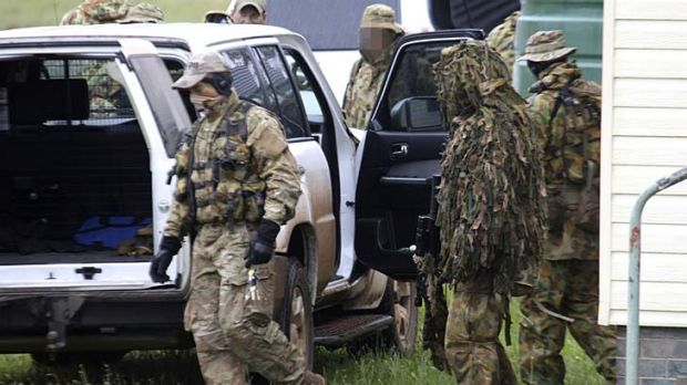 Camouflaged police are searching for Malcolm Naden.