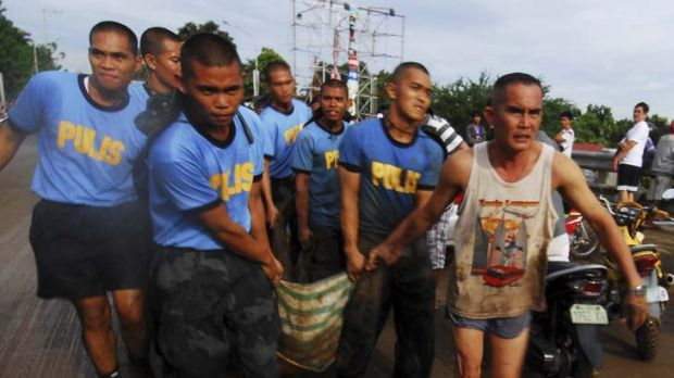 Devastation ... police carry the body of a victim of a flash flood that hit Cagayan de Oro city.