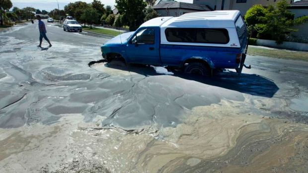 Sewage spreads on a Parklands street as liquefaction from the earthquake causes a car to become trapped in a sinkhole.