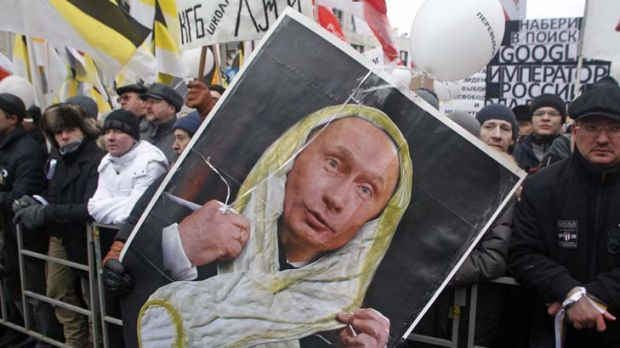 Scorned ... a protestor holds a poster showing Vladmir Putin in a white ribbon of the sort worn by protestors, which he ...