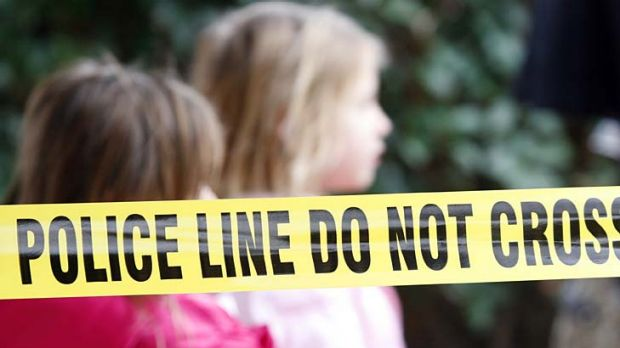 Seven dead ... two young girls walk past police tape that stretches around the apartment complex.