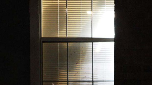 A crime scene photographer is silhouetted against blood splattered window blinds in an apartment where seven people were ...