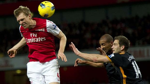 Arsenal's German player Per Mertesacker (L) heads the ball under a challenge from Wolverhampton Wanderers'  Roger ...