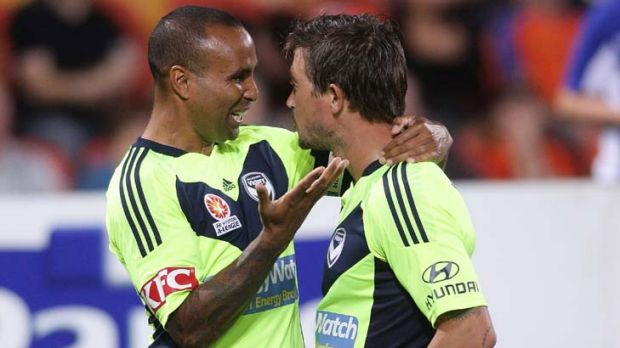 Harry Kewell celebrates with Archie Thompson after scoring a goal during against the Roar.