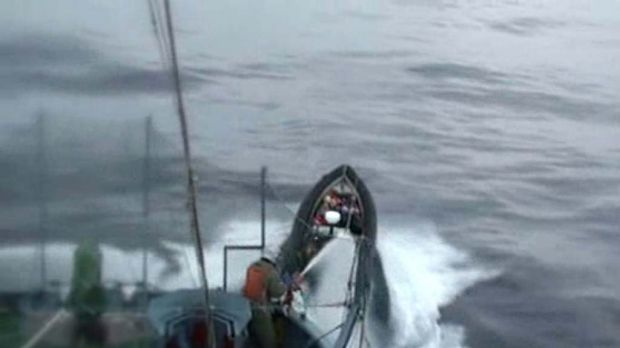 Japanese whalers from the Yushin Maru No.3 employ water cannon against Sea Shepherd activists in small boats.