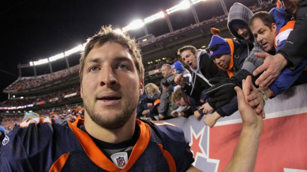 High fives .... Tim Tebow acknowledges the fans after his team's win over the Pittsburgh Steelers.