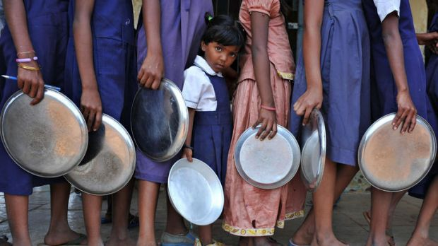 Schoolchildren queue for a midday meal as Prime Minister Manmohan Singh labels child malnutrition a national shame.