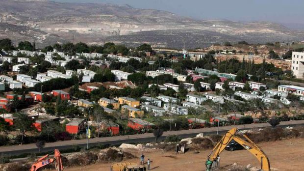 Construction vehicles prepare the ground as building of a housing project resumes in the disputed West Bank Jewish ...