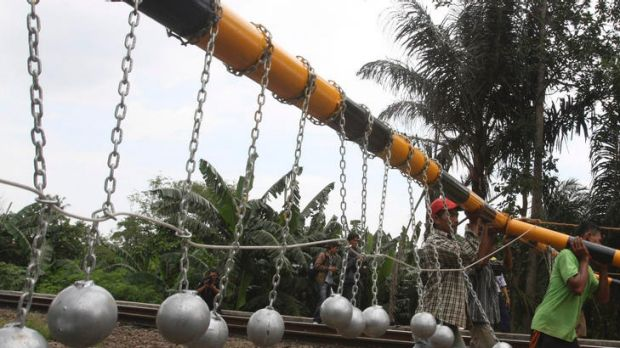 Although other deterrents have failed, Indonesian train authorities hope hanging heavy balls above train tracks, just ...