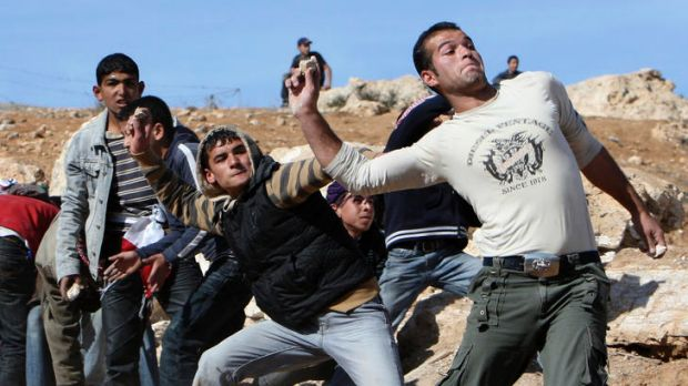 Palestinian youths throw stones at Israeli soldiers during a protest in Yatta, near Hebron.