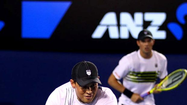 Bob Bryan plays a backhand in the fourth round doubles match as his partner, Mike, looks on.
