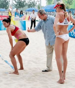 Then US-President George W Bush pats the back of US women's beach volleyball team player Misty May-Treanor (left) while ...