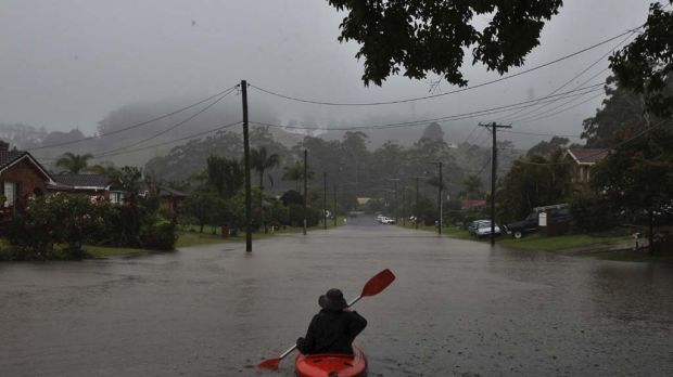 A resident in a kayak negotiates flooded streets in Coffs Harbour as torrential rain hammers the region.