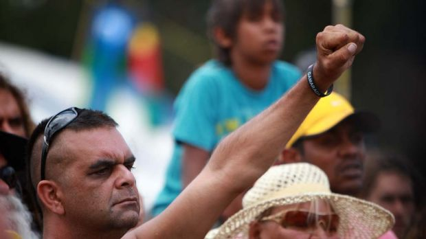 A man raises his hand as representatives  from the Aboriginal tent embassy deliver a statement to the media in Canberra ...