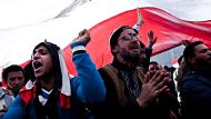 Egyptian men chant underneath a giant Egyptian flag during the first anniversary of the Egyptian revolution, Tahrir ...