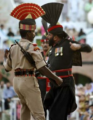 An Indian Border Security Force soldier, left, and a Pakistani Rangers soldier march during Beating the Retreat ceremony.