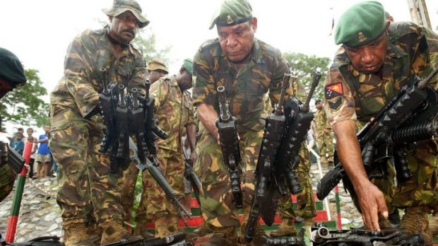 At ease: PNG soldiers at Tuarama Barracks hand back weapons to symbolise the end of the attempted uprising.
