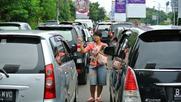 Lining up for a job: Maya Sari and her son Muhammad weave through traffic looking for a driver who needs passengers.