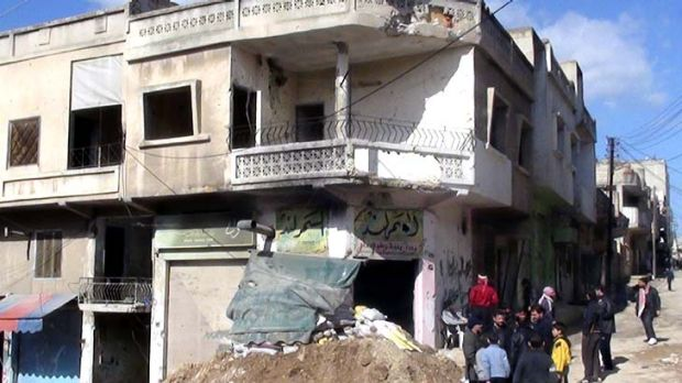 Residents stand outside the ruins of houses  near Homs after a military crackdown on protests against Syrian President ...
