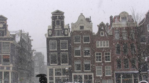 A man crosses a bridge in heavy snow in Amsterdam. A cold snap has resulted in deaths and power problems in many parts ...