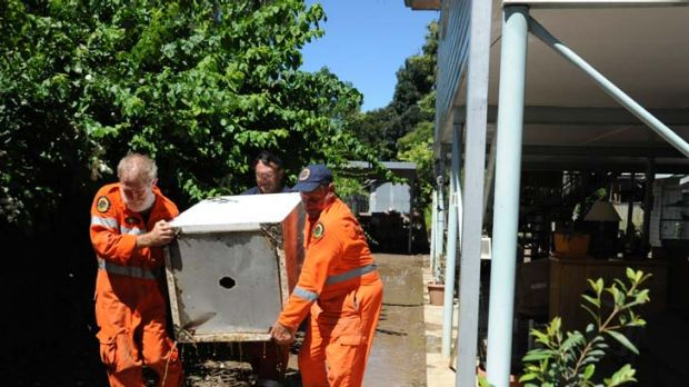 Easy does it ... State Emergency Service volunteers help remove damaged household items in Moree.