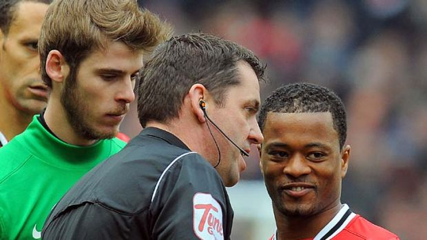 Referee Phil Dowd speaks to Patrice Evra after Liverpool striker Luis Suarez failed to shake hands with Manchester ...