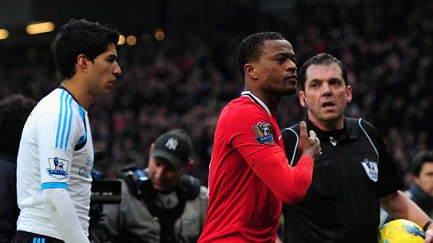 Patrice Evra of Manchester United celebrates victory as he walks off with Luis Suarez of Liverpool.