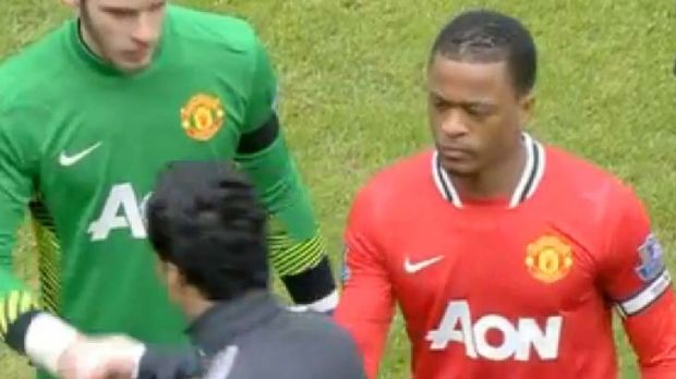 Controversial ... Luis Suarez, front, walks past Patrice Evra, right, without shaking his hand.