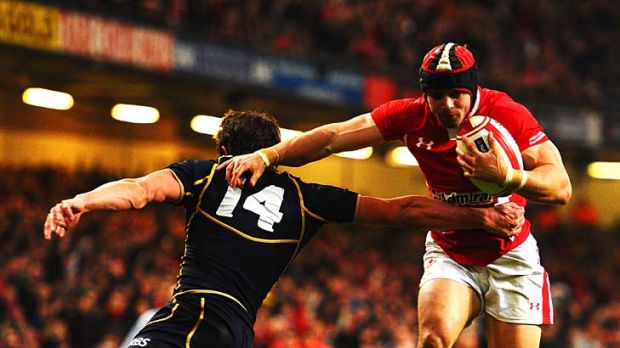 Leigh Halfpenny of Wales shakes off the tackle of Lee Jones of Scotland to score a try.
