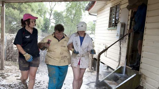 Trying time … volunteers help Patricia Budd as she returns to her home in Mitchell, about 500 kilometres west of ...