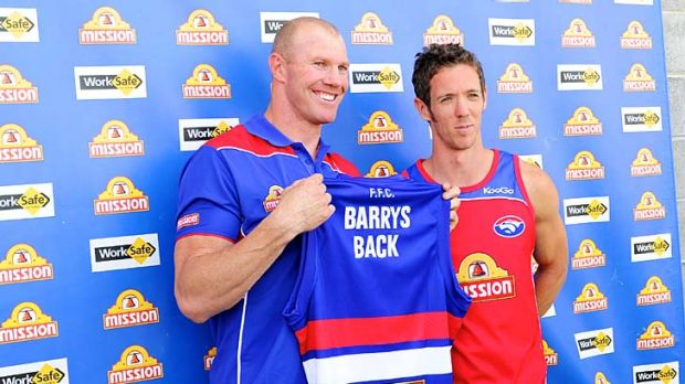 Once bitten: Barry Hall (left) receives his guernsey from Bob Murphy in his welcome back to the kennel yesterday.