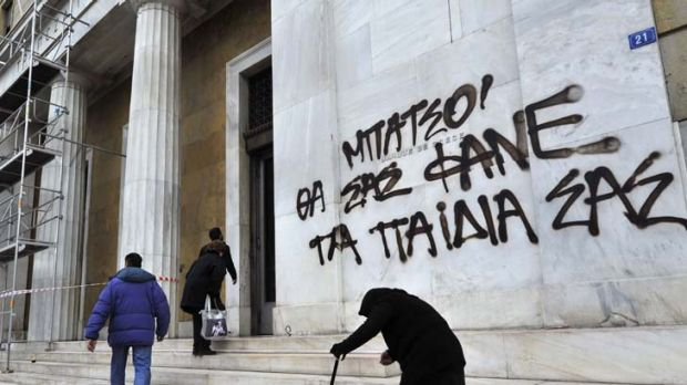 Despair .. an elderly woman begs by the Bank of Greece in Athens. A slogan reads: ''Cops, your children will eat you.''