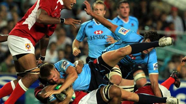Diving in … youngster Tom Kingston is tackled in the Waratahs' trial match against Tonga at the SFS on Friday night.