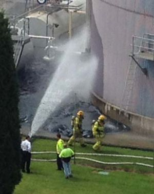 Emergency workers spray water on the chemical spill.