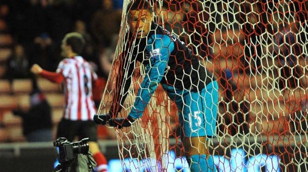 Down and out: Arsenal's Alex Oxlade-Chamberlain after his own goal helped Sunderland to victory.