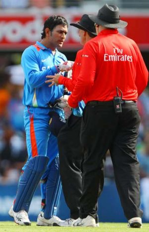 M.S Dhoni talks with umpires after Hussey was called back to the crease.