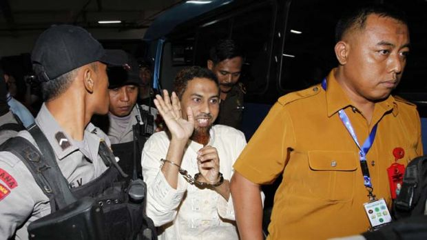 Umar Patek waves to journalists as he arrives at court in West Jakarta.