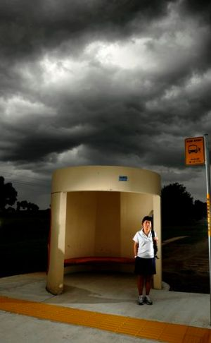 Yue Li waits for a bus under heavy skies after leaving work at Geoscience Australia in Symonston.