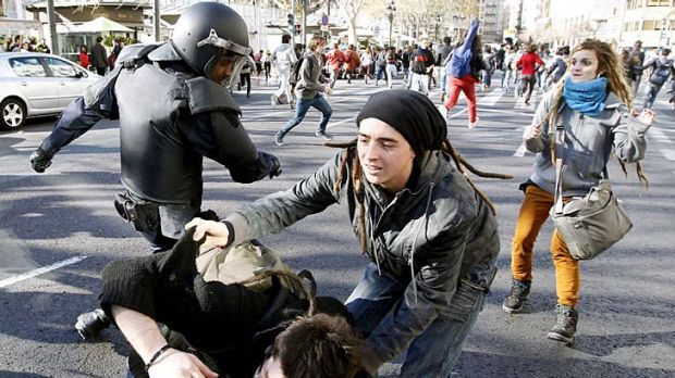 A riot policeman wields his baton during clashes in Valencia.