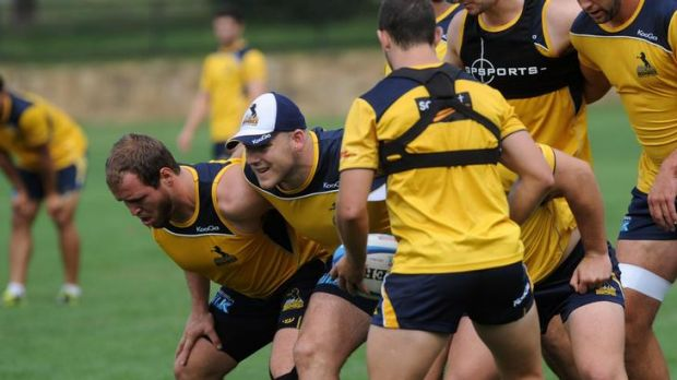 Brumbies player Nic White feeds the ball  into the scrum   including hooker  Stephen Moore , centre, at training at ...