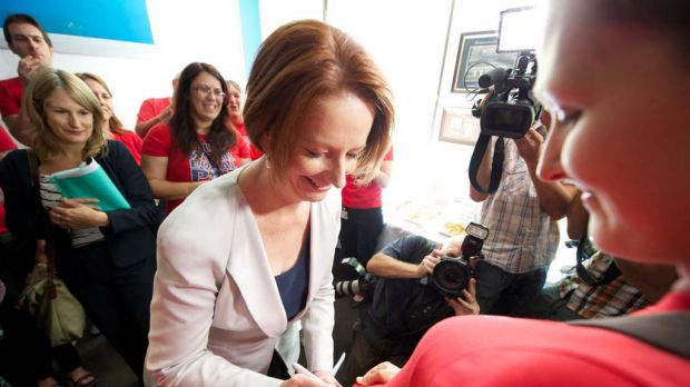 Prime Minister Julia Gillard signs a nures union campaign shirt during a visit to the Melbourne City Mission this morning.