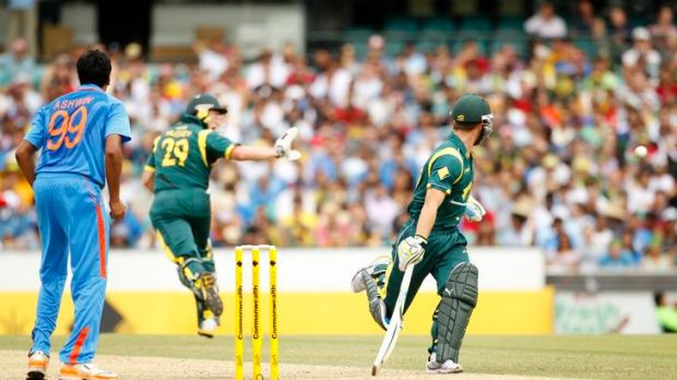 India's Ravichandran Ashwin (left) and Australia's Matthew Wade (right) watch as David Hussey (centre) fends off a ...