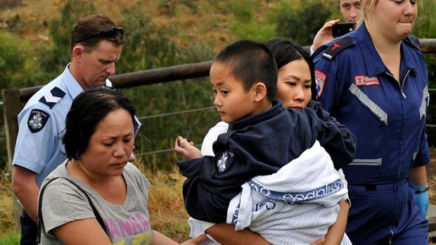 Ryan Pham is carried to safety by his mum after he was pulled from the sodden, swollen creek this morning.