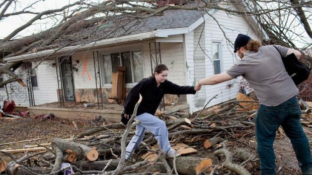 Damage ... Harrisburg residents climb over downed limbs as they leave their house.