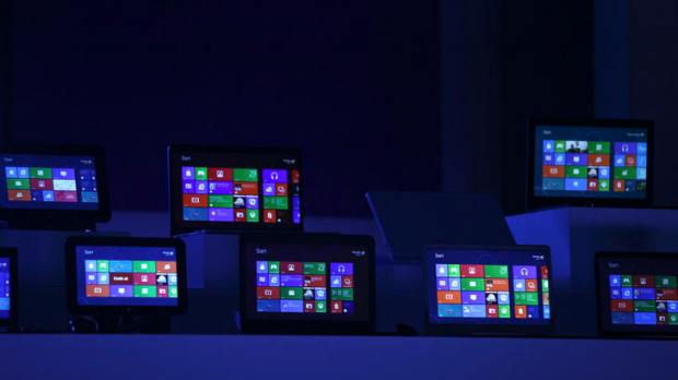 The Windows 8 software homepage is displayed on tablet devices at the Microsoft  Windows 8 software consumer preview ...