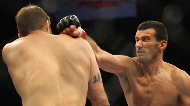 Anthony Perosh of Australia punches Nick Penner of Canada.