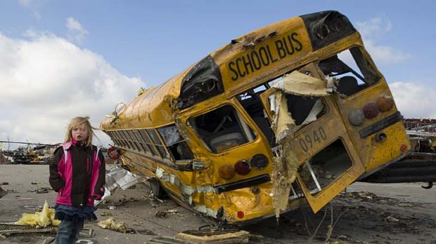 Student Madeline Evans walks past a destroyed school bus after a tornado devastated the town of Henryville, Indiana.