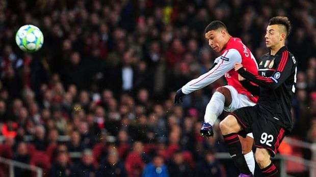 Arsenal striker Alex Oxlade-Chamberlain (L) shoots past AC Milan's Stephan El Shaarawy.