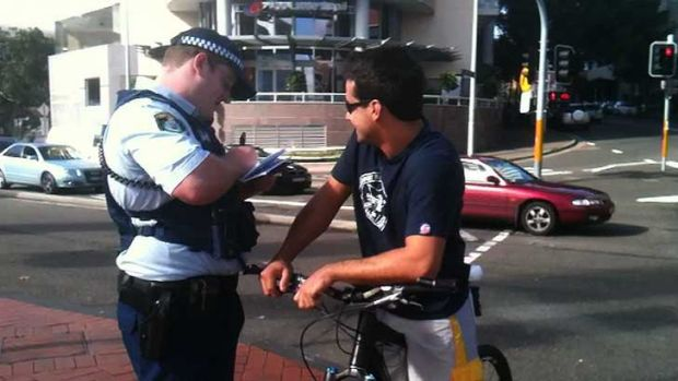 Just the ticket ... a cyclist falls foul of the police on Pyrmont Bridge.